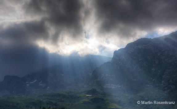 Sonnenlicht scheint durch die Wolken ins Tal